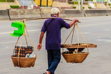 84333205-street-hawker-is-walking-with-carry-bamboo-baskets-of-grilled-eggs-on-shoulder-pole-go-around-bangko.jpg